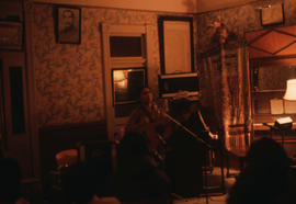 Man playing guitar in a room decorated with a portrait of Dr. Sun Yat-sen