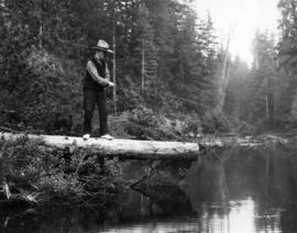 Mayor L.D. Taylor standing on log, fishing in lake