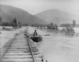 Man in rowboat on floodwaters at washed out railroad tracks