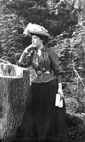 [Mrs. H.W. Maynard standing next to tree stump, near Brockton Point, Stanley Park]