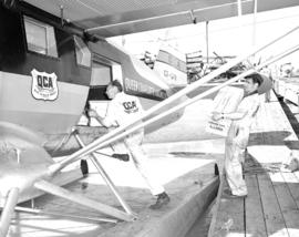 [Queen Charlotte Airlines personnel loading supplies onto a float plane]