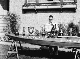 Mr. Graham [and dog] posing with speed boat and trophies
