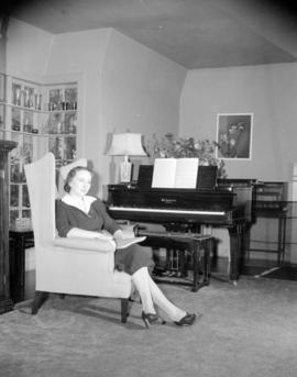 [Woman seated in an armchair by a piano in a living room]