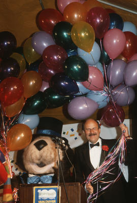 Tillicum beside Mike Harcourt holding balloons on stage at Vancouver's 99th birthday celebra...