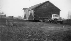 Moving old prison camp buildings to sugar factory site for bunk houses, cook shack and office bui...