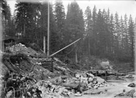 [Winch and other equipment on partially cleared hillside next to stream]