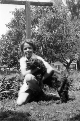 [Mary Louise Taylor in yard with dog]