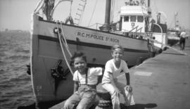 "[Two boys sitting next to R.C.M.P. ship ""St. Roch"" at Embarcadero dock in San Diego, Ca..."
