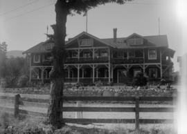 Building with a stone fence in front, possibly Bowen Island Lodge