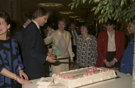 Gordon Campbell and group beside cake at Legacies Program event at The Bay