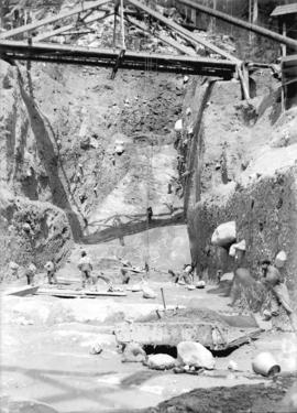 [Men excavating area underneath scaffolding and pulleys for Buntzen Lake Power Plant number one]