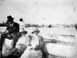 [L.D. Taylor sitting on beach at Summit Lake with two unidentified women]