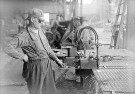 [Man using machine to cut or drill metal sheets]