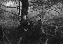 Portrait of two women with a dog under tree