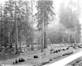 Stanley Park, visitors seated on grass facing east near Bandstand