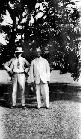 [Two men standing in front of a tree]