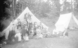 [Group of men, women and children assembled in front of tents]