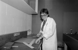 Volunteer Liz Croome working in the preservation lab at the City of Vancouver Archives