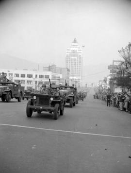[Military vehicles passing by crowds in a parade along Burrard Street]