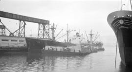 S.S. Valor [at dock, with lumber-filled barges alongside]