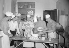 [Group of people, some in military uniform, in a kitchen baking]