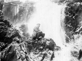 [Unidentified man sitting by a waterfall]