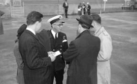 [Vice Admiral Percy W. Nelles talking with reporters at the airport]