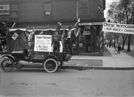 "[Truck outside Stuart Thomson's studio/shop decorated with banners ""Stuart Thomson offi..."