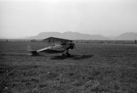 [View of biplane in field]