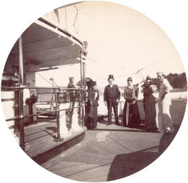 "[An unidentified man and three women on the deck of H.M.S. ""Warspite""]"