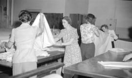 [Women folding sheets at Nelson's laundry]