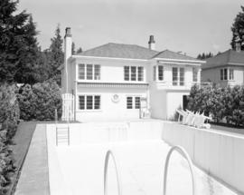 [Rear view of a house with a drained swimming pool]