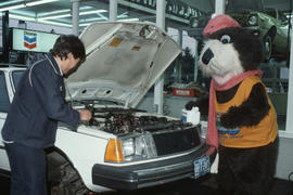 Tillicum looking under the hood of a car at Tremblay and Sons Chevron Station on 4th Avenue and M...