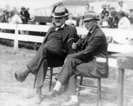 Two unidentified men sitting on fairgrounds