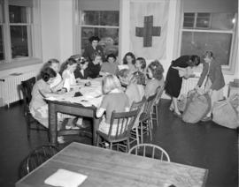 [Girls folding newsletters and reading letters at the Junior Red Cross]