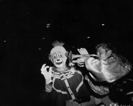 Clown and man blowing trumpet in P.N.E. Shrine Circus performance