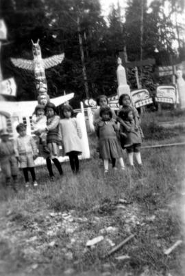[First Nations children in front of totem poles at] Alert Bay