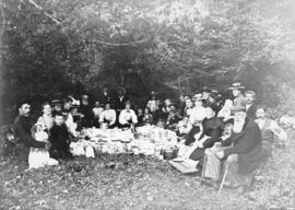 [Group of men, women, and children at a picnic in a small clearing]