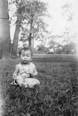 Baby seated in the grass