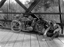 [James Crookall sitting and smoking a pipe beside a motorcycle]