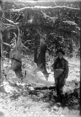 [Roy Hood with a hanging deer and buck]