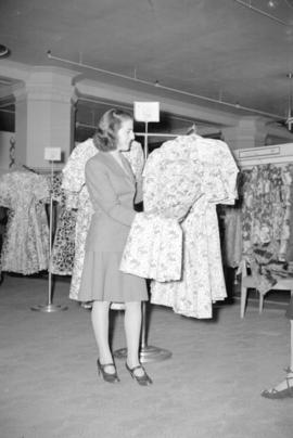 [Woman looking at dresses in a store]