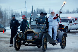 Day 95 Torchbearer 5 Marl Brown carries the torch on an old car in Fort Nelson, British Columbia