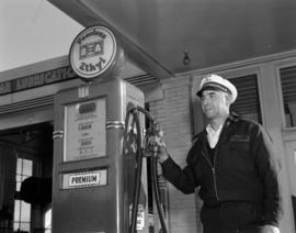 [Harry Howe's service station attendant at a gas pump]