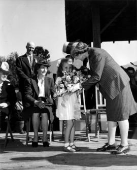 Young girl presenting flowers to Mrs. Woodward at Boys' and Girls' Department event