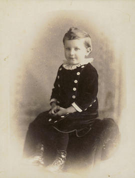 [Studio portrait of young boy, seated on back of lounge chair]