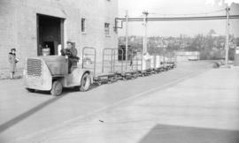 [Airman towing trolleys with a small truck at the R.C.A.F. equipment depot #2]