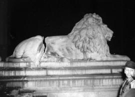 [Side view showing damage to the lion statue on the courthouse steps]