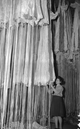 [Woman working on parachutes hanging at the R.C.A.F. equipment depot #2]