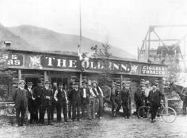 [Men standing in front of the Old Inn]